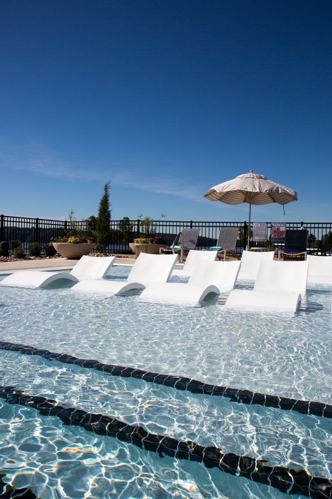 Lounge chairs in the pool's shallow end keep sunbathers cool.